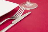 Elegant place setting on red tablecloth — Stock Photo