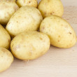 Stock Photo: Jersey Royal new potatoes on wooden chopping board