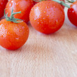 Ripe cherry tomatoes on  a wooden chopping board — Stock Photo