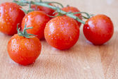 Ripe cherry vine tomatoes on a wooden chopping board — Stock Photo