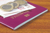 British passport with Euro coins and notes on wooden table — Stock Photo