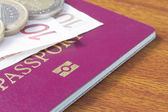 British passport with Euro coins and notes on wood table — Stock Photo