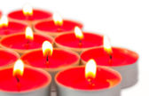 Glowing red tea lights on white — Stock Photo