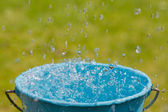 Rain falling into full bucket of water — Stock Photo