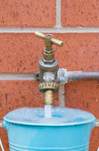 Outside tap on brick wall filling a blue bucket — Stock Photo