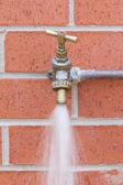 Outside tap on brick wall wasting water — Stock Photo