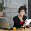 Mature businesswoman with writing pad — Stock Photo