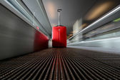 Blurred moving escalator with red trolley in airport — Stock Photo