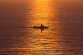 A navy boat sailing into the setting sun — Stock fotografie