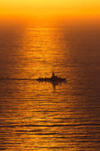 A navy boat sailing into the setting sun — Stock Photo