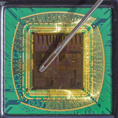 Open computer chip with gold wire connections compared to a needle — Stok fotoğraf