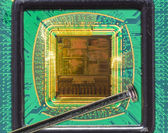 Open computer chip with gold wire connections compared to a needle — Stock Photo