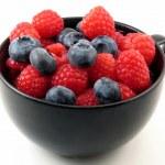 Fresh berries in black cup — Stock Photo