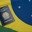 Brazilian passport over a Brazilian flag — Stock Photo