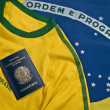 Brazilian passport over a Brazilian jersey and flag — Stock Photo