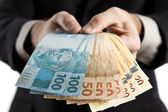 Business man showing you brazilian money. — Stock Photo