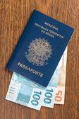 Brazilian Passport with real bills — Stock Photo
