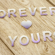 Forever yours on wooden background — Stock Photo #32176663
