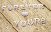 Forever yours on wooden background — Stock Photo