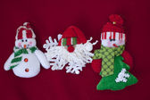 Santa claus and two snowmen on red background — Stock Photo