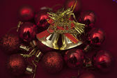Gold merry christmas bells with red ornaments — Stock Photo
