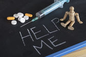 Syringe, pills and wooden human figure on chalkboard with help me — Photo