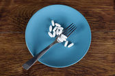 Weight loss concept diet pills on plate with fork — Stock Photo