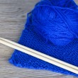 Skein of blue knitting yarn with bamboo needles and completed knitting — Stock Photo #44586293