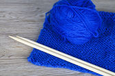 Skein of blue knitting yarn with bamboo needles and completed knitting — Stock Photo