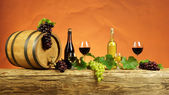 Red and white wine bottle with white and grapes — Stock Photo