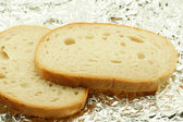 Slices of bread on a white foil — Stock Photo
