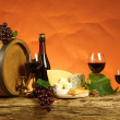Stock Photo: Red wine, barrel,chesse and bottles