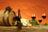 Red wine, barrel,chesse and bottles — Stock Photo