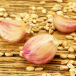 Garlic cloves on chopping board — Stock Photo #27497865