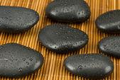 Black stones on wood background — Stock Photo