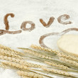 Raw dough heart-shaped and spikelets of wheat — Stock Photo