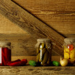 Jars of pickled vegetables on wooden shelves — Stock Photo