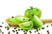 Green tomatoes with spoon — Stock Photo