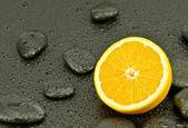 Orange with spa stones — Stock Photo
