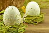 White pierced easter eggs in a nest of hay — Stock Photo