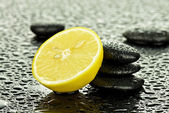 Wet lemon with basalt stones — Stock Photo