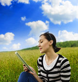 Girl with tablet pc on the grass. — Stock Photo