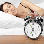 Brunette woman turning off her alarm clock — Foto Stock