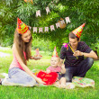 Young family celebrating the first birthday of their child in th — Stock Photo