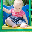 Cute baby girl sitting on a swing at the playground — Stock Photo