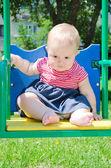 Bambina carina seduta su un'altalena al parco giochi — Foto Stock