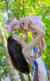 Mom picks up baby girl — Stock Photo