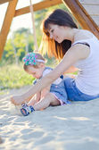 Mother and daughter on sand — Stock Photo