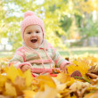 Baby girl in the leaves — Stock Photo
