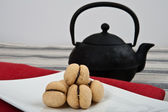 """Italian cookies called """"baci di dama"""" on a white plate with a red cloth and a big black teapot. — Foto Stock"""